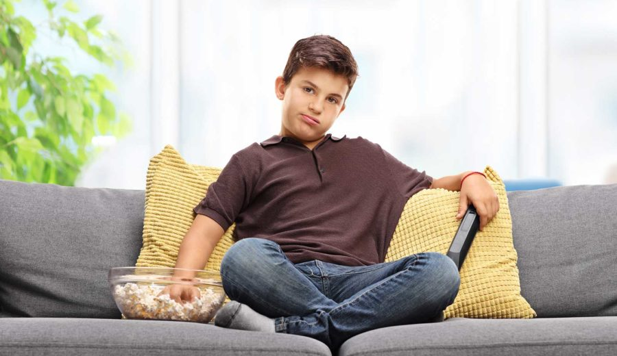 Bored kid on couch watching TV