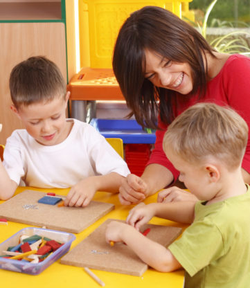 Teacher and three preschoolers doing arts and crafts with wooden blocks