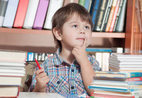 Preschooler sitting at a table with books