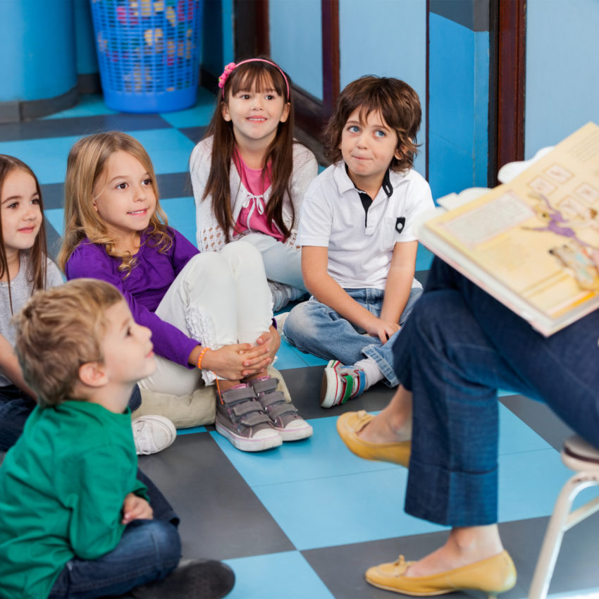 Teacher Reading Book To Preschool Children