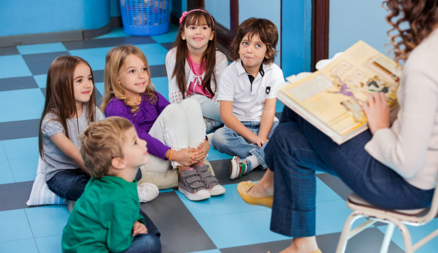 Teacher Reading Book To Preschool Children