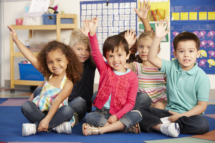 Group Of Preschoolers Answering Question In Class