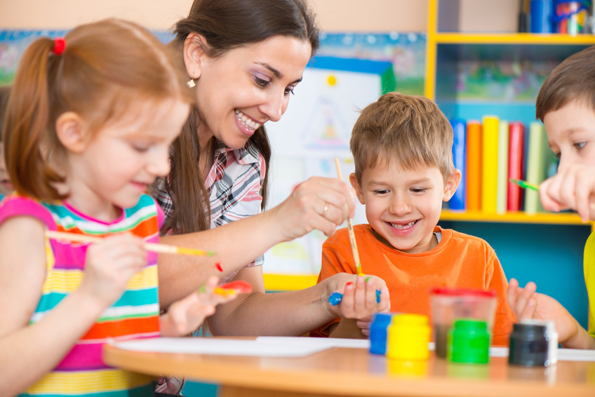 Preschool children drawing with teacher in art class
