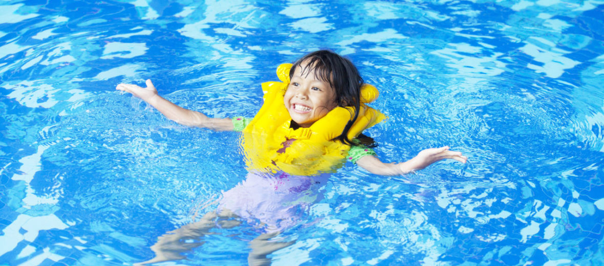 Toddler/Preschooler swimming in the pool with life jacket on for safety