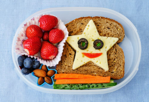 School lunch box for preschooler or toddler kids with healthy food in the form of funny faces
